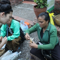 Teaching me how to eat the sticky rice inside bamboo